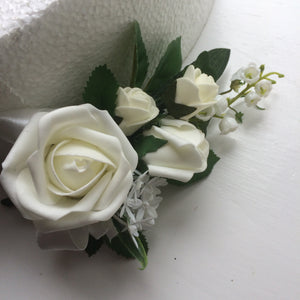 A corsage featuring lily of the valley & ivory foam roses