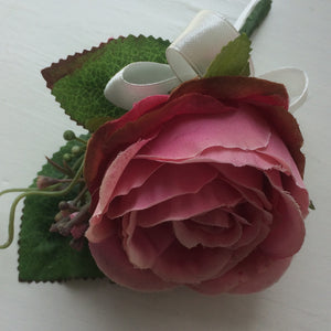 a silk buttonhole featuring pink rose and ivory bow