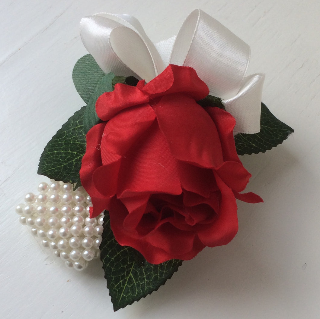 wrist corsage featuring a red silk rose