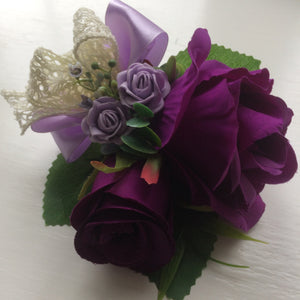 A corsage featuring artificial purple & lilac roses & vintage lace bow