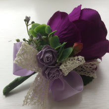 A buttonierre featuring artificial purple & lilac roses