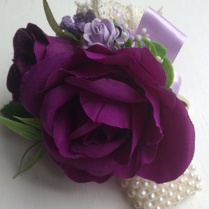A wrist corsage featuring artificial purple & lilac roses & vintage lace bow