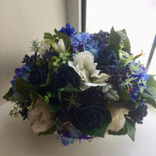 A flower arrangement of cream & blue artificial flowers & foliage