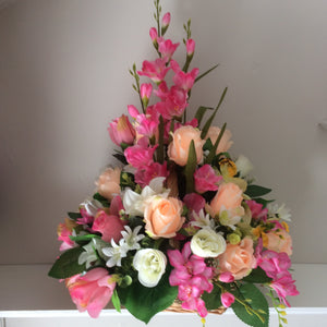 A large bespoke front facing flower arrangement in wicker basket
