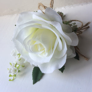 a buttonhole featuring lily of the valley & a white or ivory silk rose