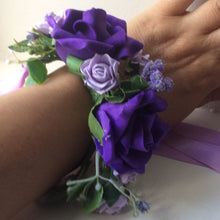 A wrist corsage featuring artificial purple & lilac roses