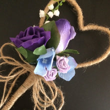 A rustic heart shaped wand with a cluster of purple and lilac flowers