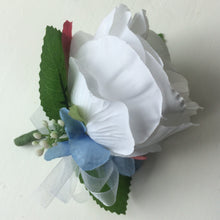 a silk buttonhole featuring a single open white rose