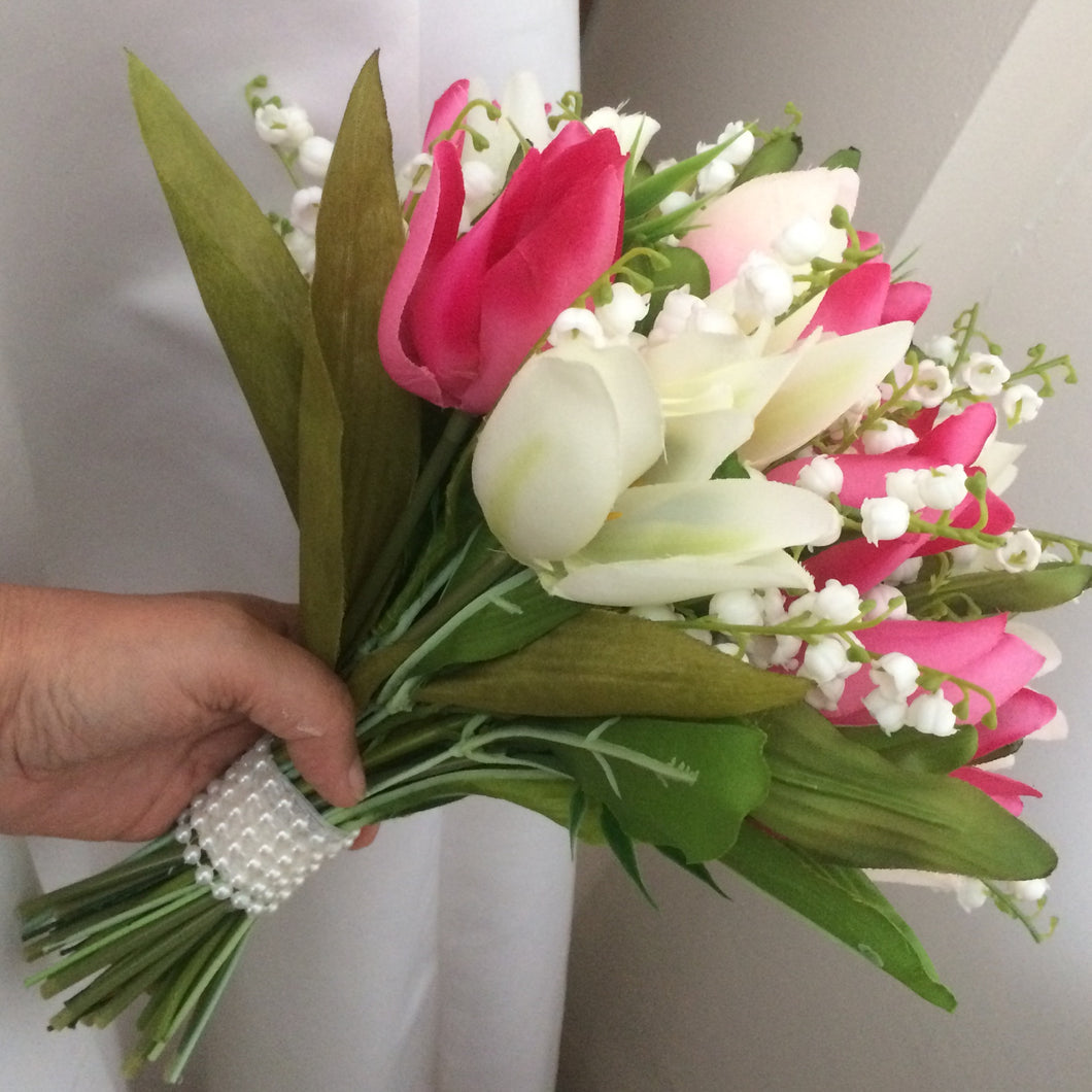 a wedding bouquet of pink and ivory tulips and lily of the valley