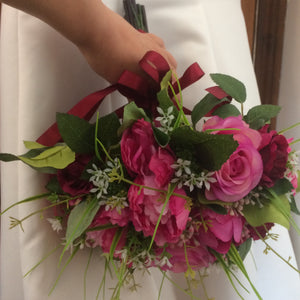 a wedding bouquet of deep pink and burgundy flowers