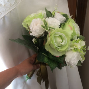 A wedding bouquet of green and white artificial silk roses