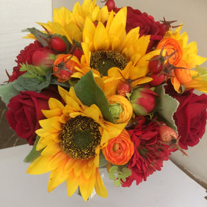 a brides wedding bouquet featuring artificial silk roses & sunflowers