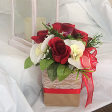 flower arrangement of artificial red roses & orchids in a gift bag