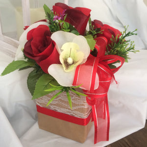 artificial red roses and orchids in gift bag