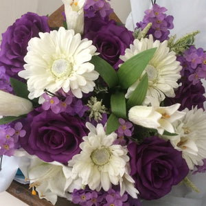 a large gift bouquet of purple and ivory flowers