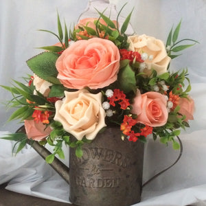 artificial flower arrangement in shades of orange and peach