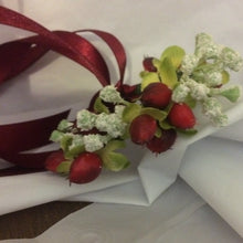 A wrist corsage featuring a hypericium berries and gypsophila
