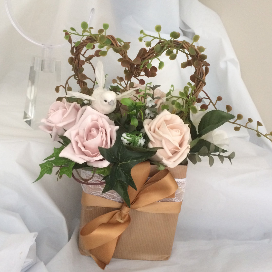 flower arrangement of artificial mocha foam roses in a gift bag