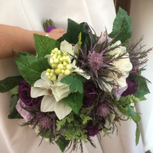 a bouquet of lilies, hydrangea, roses and thistles