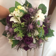 a wedding bouquet of ivory and purple artificial flowers