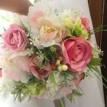 A bridal bouquet of artificial silk pink silk rose peony and berries