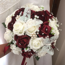 A wedding bouquet of artificial ivory & burgundy rose flowers