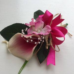 a corsage featuring a calla lily, hydrangea & ribbon bow