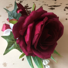 A buttonhole featuring a burgundy rose, lily of the valley & hydrangea