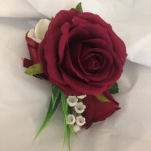 A corsage featuring burgundy roses, lily of the valley & hydrangea