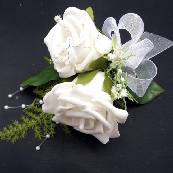 an artificial wedding corsage of two ivory foam roses with asparagus fern
