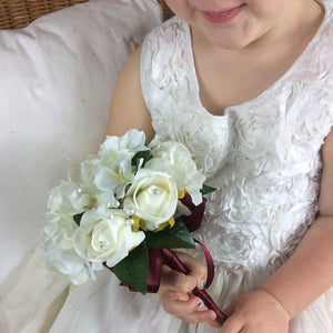 flower girl holding a posy of ivory flowers