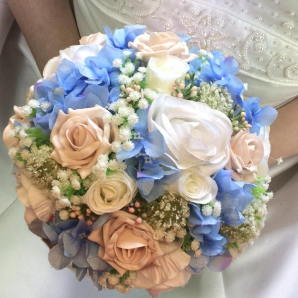 A brides bouquet of ivory mocha and blue artificial silk flowers
