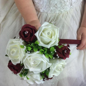 flower girl holding a posy of artificial ivory and burgundy foam roses