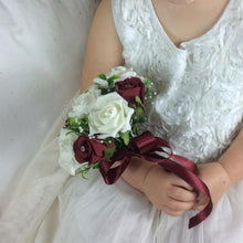 bridesmaid holding a posy of ivory and burgundy roses