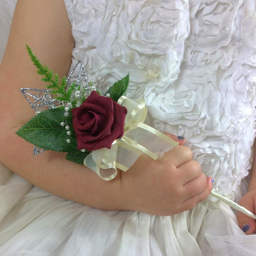 a burgundy rose and cream ribbon decorate a silver metal wand