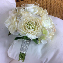 artificial wedding bouquet featuring champagne and ivory flowers
