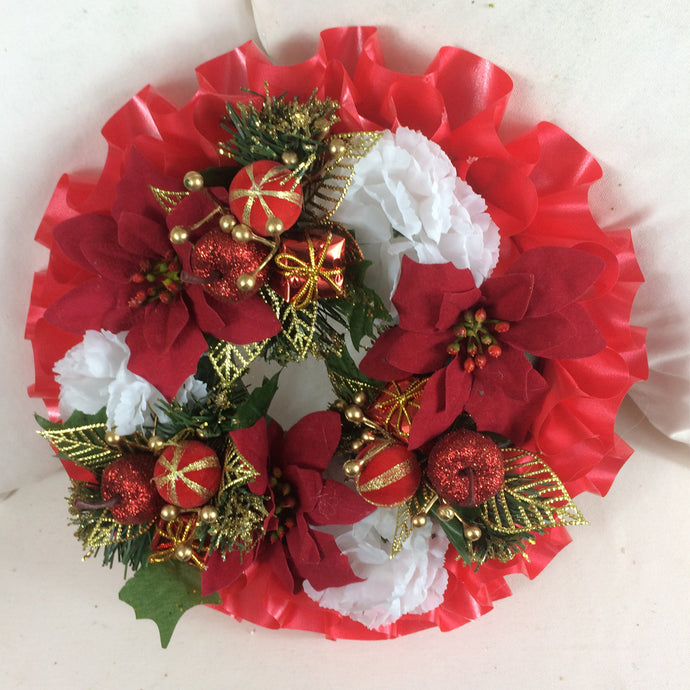 a memorial christmas wreath featuring parcels, carnations & poinsettia