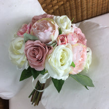 A brides bouquet of pale pink and ivory silk roses & peony flowers