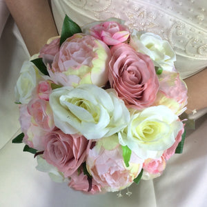 a bridal bouquet of dusky pink and ivory flowers