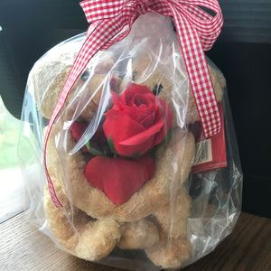 2 cuddly bears with linked arms holding a red soap rose and plush heart