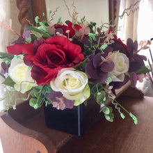 a large flower arrangement of red & ivory roses