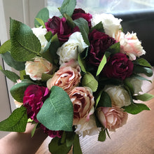 - A wedding bouquet of peach, ivory and burgundy silk roses