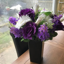 a large hand tied flower arrangement in black square vase