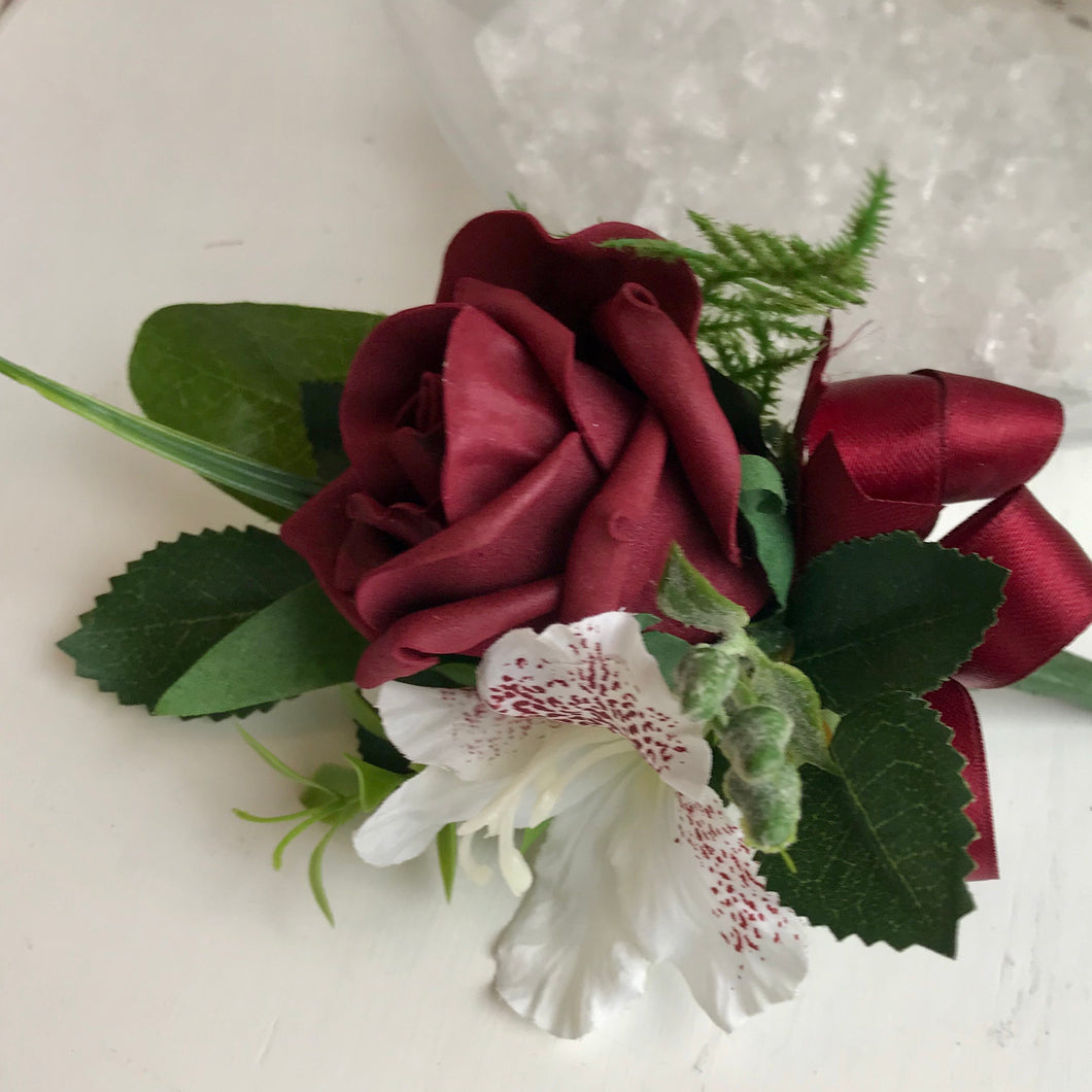 A wedding corsage featuring a bugundy foam roses and hydrangea