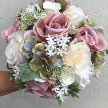 - A wedding bouquet of ivory and dusky pink artificial flowers