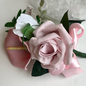 A pink corsage featuring calla lily and roses