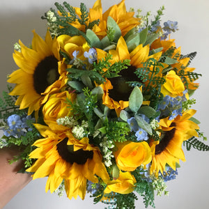 - a brides bouquet of sunflowers roses and blue forget-me-nots