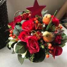 a christmas table centrepiece of red and ivory flowers