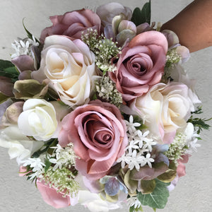 A wedding bouquet of ivory and dusky pink artificial flowers