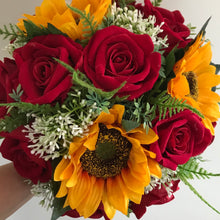artificial red roses and sunflowers feature in this wedding bouquet
